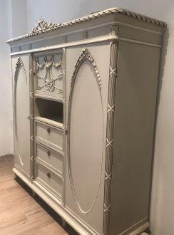 Шкаф с резьбой жемчужного цвета.